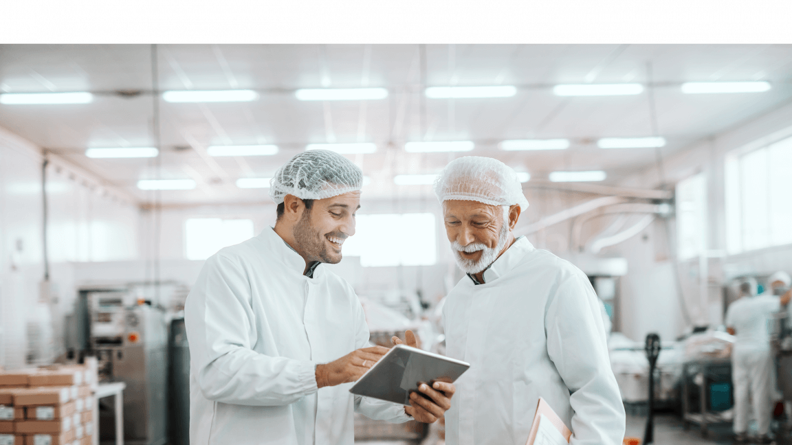 2 men working in a warehouse wearing white overcoats and hairnets