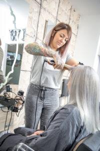 A hairdresser straightening a clients hair